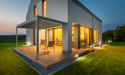External view of a new house at night with patio and outdoor lighting